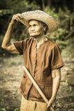 老亚裔妇女在庭院里 免版税库存图片