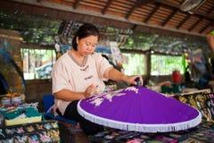 老亚洲妇女开会,绘画一把紫色木伞 免版税库存照片