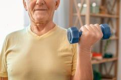 老人与哑铃的锻炼在家医疗保健在一个手特写镜头 免版税库存图片