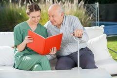 老人与女性看守者的阅读书 免版税库存照片