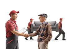 老人与搬家工人握手,运载长沙发i的搬家工人 图库摄影