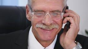 老人与白色智能手机讲话在办公室 关闭 股票视频