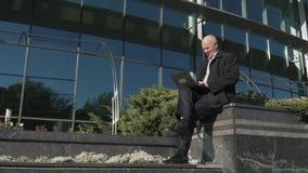 老人与膝上型计算机一起使用在城市 影视素材