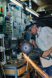 老人与角度研磨机一起使用 免版税库存照片
