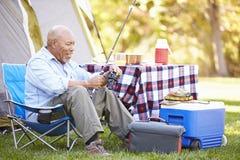老人与钓鱼竿的野营假日 库存照片