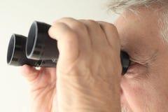 老人举行的双筒望远镜 免版税库存图片