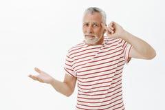 老人事少年丢失了头脑,疯狂 在镶边T恤杉辗压的迷茫和生气的资深有胡子的男性 免版税库存图片