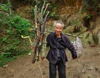 老人亚洲人,有束柴把的,在山行迹去。 免版税库存照片