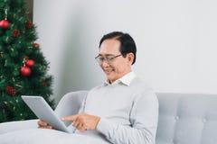 老人使用一种数字式片剂并且微笑着,当休息o时 免版税库存图片