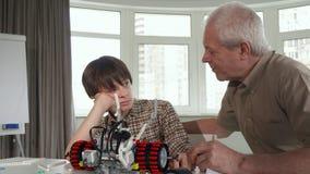 老人发现玩具车的零件他的孙子的 库存图片