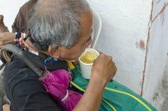 老人吃一个杯子稀饭的窗帘叫化子 免版税库存照片
