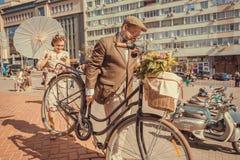 老人和他的夫人冲对节日减速火箭的巡航的美丽的葡萄酒服装的 免版税库存照片