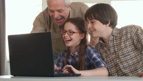 老人和他的孙在膝上型计算机招待 免版税图库摄影