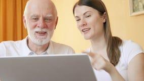 老人和女儿在家有录影闲谈通过膝上型计算机的信使app 微笑的挥动的手 股票视频