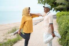 老人和妇女互相支持,当舒展时 库存图片