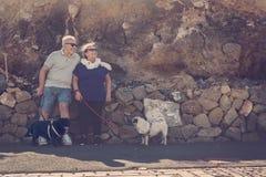 老人和妇女有两个哈巴狗的看太阳 库存照片