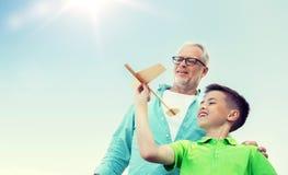 老人和男孩有玩具飞机的在天空 免版税图库摄影