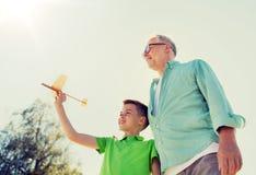 老人和男孩有玩具飞机的在天空 免版税库存照片