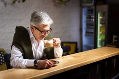 老人喝咖啡在酒吧 免版税库存图片