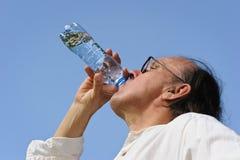 老人喝从瓶的水 库存照片