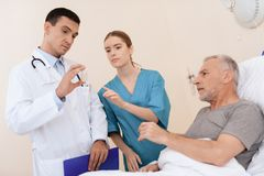 老人在一个轻便小床说谎在内科病房里,并且在他旁边有医生和护士 免版税库存图片
