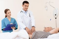 老人在一个轻便小床说谎在内科病房里,并且在他旁边有医生和护士 库存照片