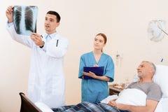 老人在一个轻便小床说谎在内科病房里 在他旁边是医生和护士 图库摄影