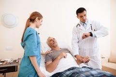 老人在一个轻便小床说谎在内科病房里 在他旁边是医生和护士 库存照片