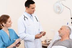 老人在一个轻便小床说谎在内科病房里 在他旁边是医生和护士 库存图片