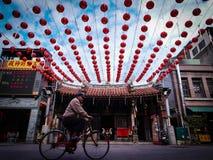 老人在亚洲寺庙前面的骑马自行车 免版税库存图片