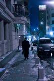老人在冬天夜街道上去 免版税库存图片