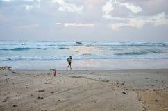 老人在冬天风雨如磐的海滩快速地走 免版税库存图片