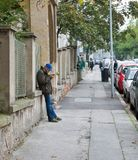老人在城市街道上的读书报纸在布拉索夫,斯洛伐克 库存照片
