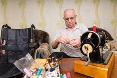 老人在家使用葡萄酒缝纫机 免版税图库摄影