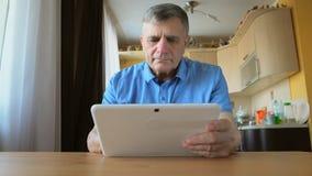 老人在家坐并且使用一台白色片剂个人计算机 免版税库存照片