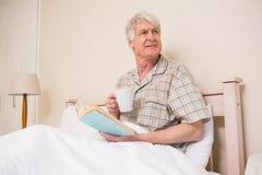 老人在床上的读一本书 免版税库存图片
