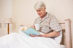 老人在床上的读一本书 免版税库存照片