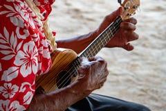 老人在法属波利尼西亚递演奏hukulele 库存照片