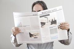 老人在灰色背景的读书报纸 免版税图库摄影