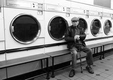 老人在自动洗衣店 免版税库存图片