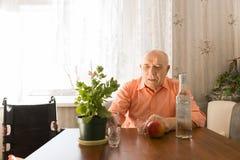 老人在表上用酒、苹果计算机和植物 免版税库存照片