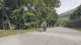老人在路的骑马摩托车在热带村庄风景 驾驶摩托车的成熟人,当moto旅行在时 影视素材