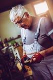 老人在车间 人划分木头 免版税库存照片