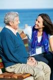 老人坐与女儿的长凳 免版税库存照片
