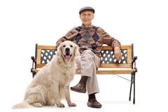 老人坐与他的狗的一条长凳 库存照片
