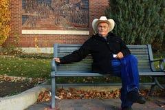老人坐公园长椅 免版税库存照片