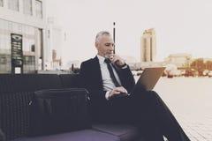 老人坐在街道的沙发 他拿着在他的膝部的一台膝上型计算机 免版税库存照片