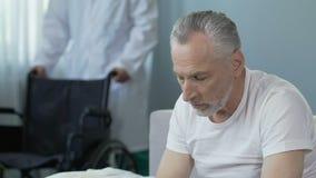 老人坐床,带来轮椅,人的护士看照相机 股票录像