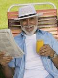 老人坐拿着报纸和橙汁的草椅举起了看法画象。 库存图片