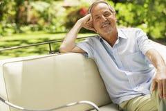 老人坐沙发在后院 库存照片